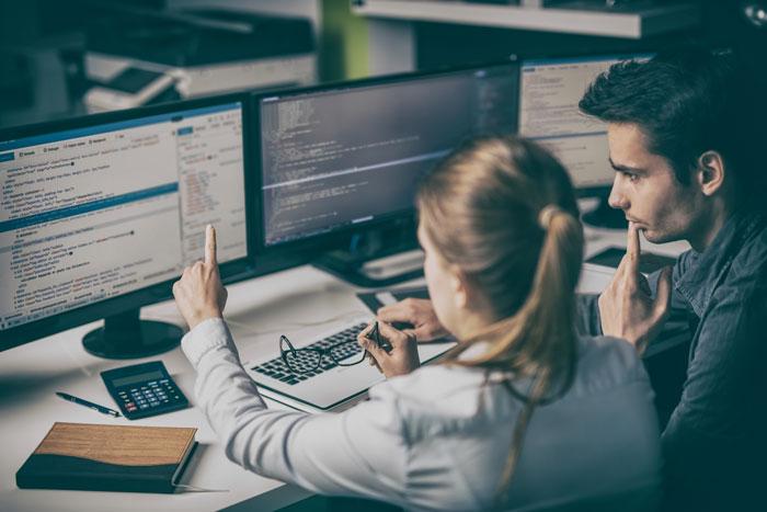A woman and man looking at a computer screen.